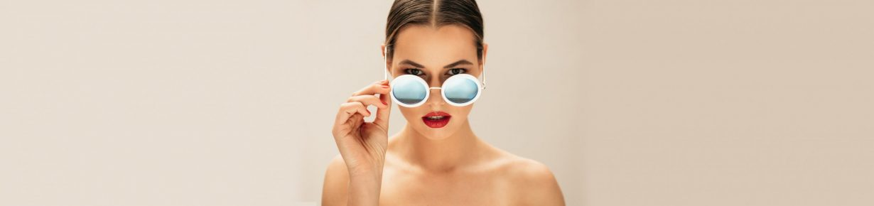 Portrait of fashion woman peeking over sunglasses. Female fashion model posing against beige background.